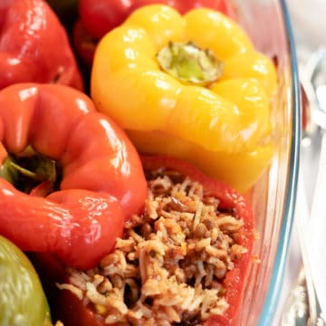 red, yellow and green capsicums stuffed with rice and lentils in a glass dish