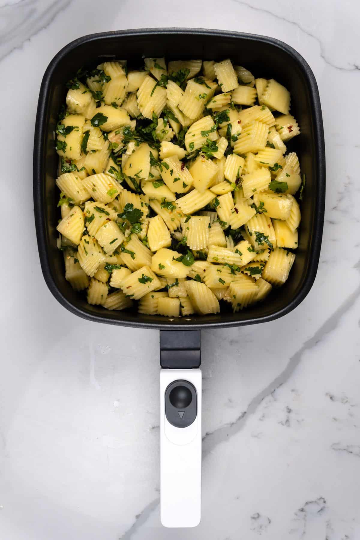 raw batata harra in an air fryer pan