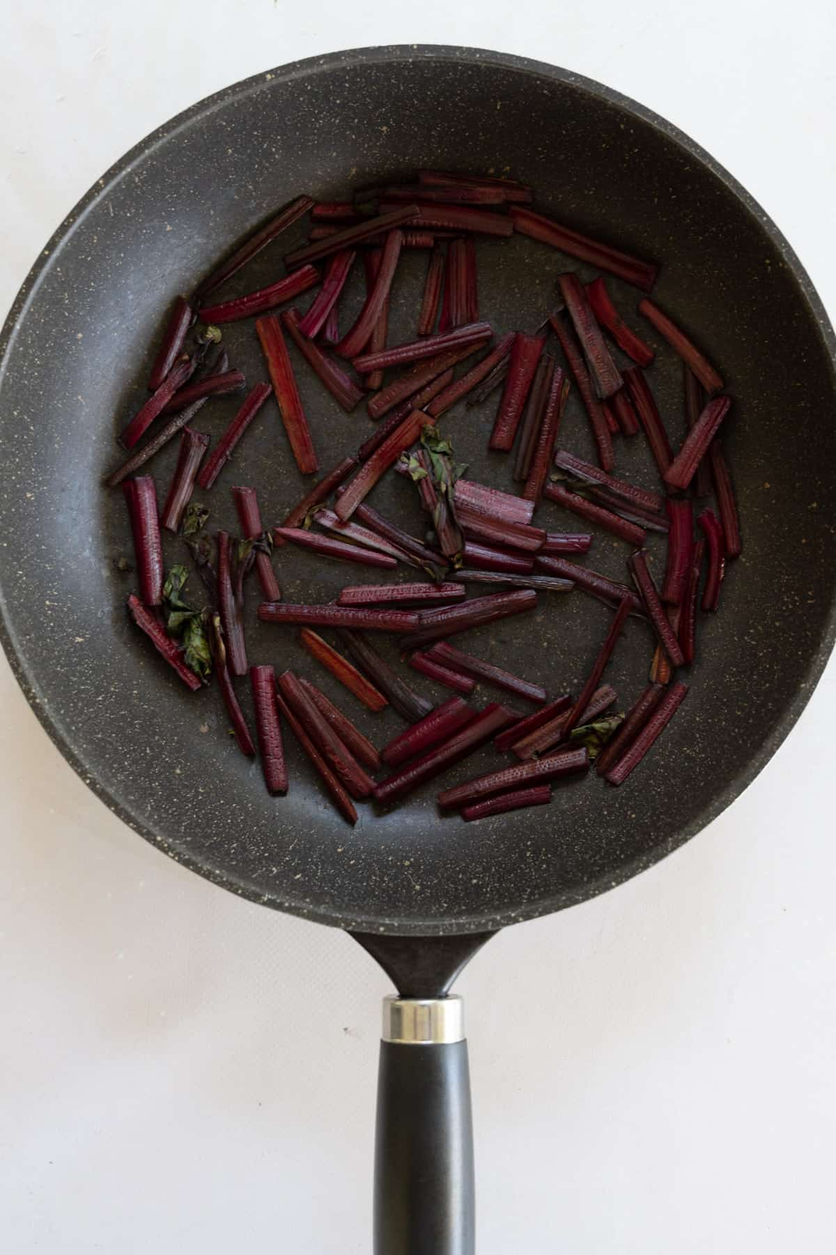 sauteed beetroot stems without oil in a black pan