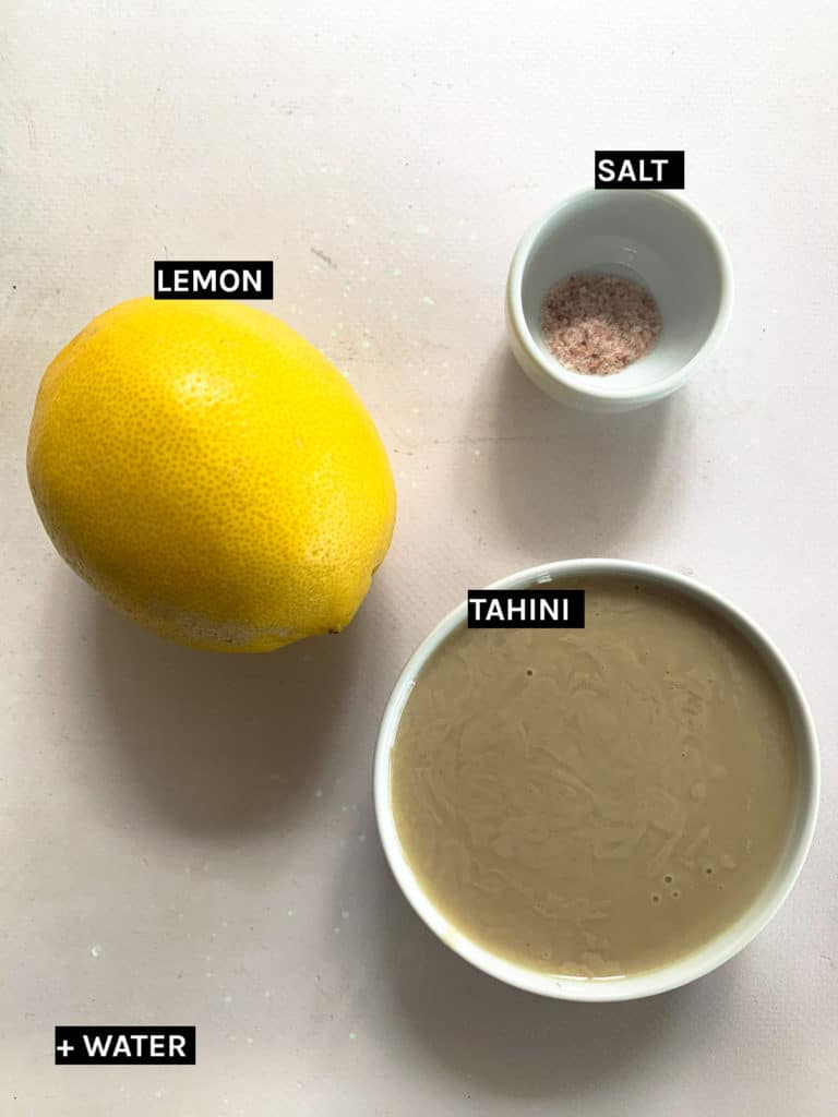 one lmeon and two separate white bowls of tahini and salt