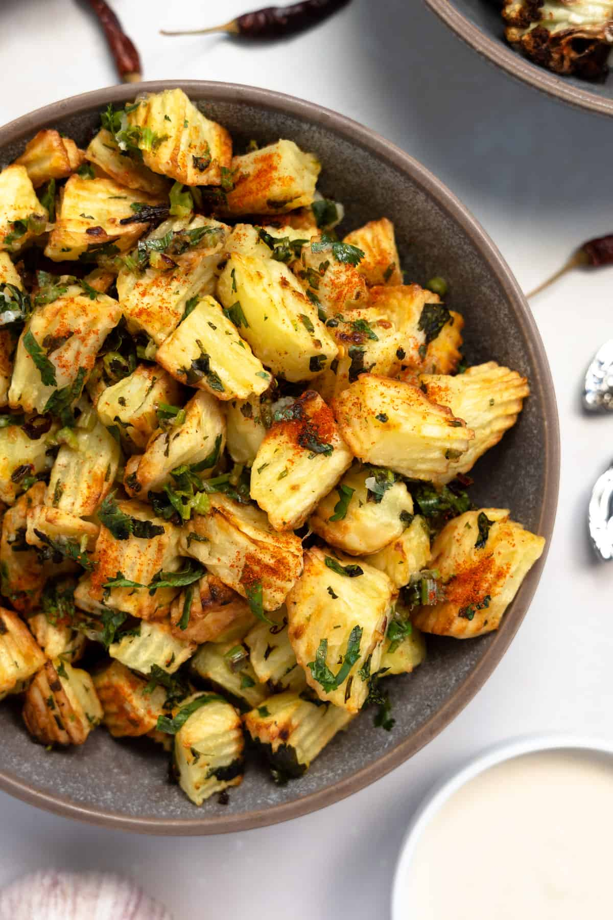 batata harra in a grey bowl with chillis on the side