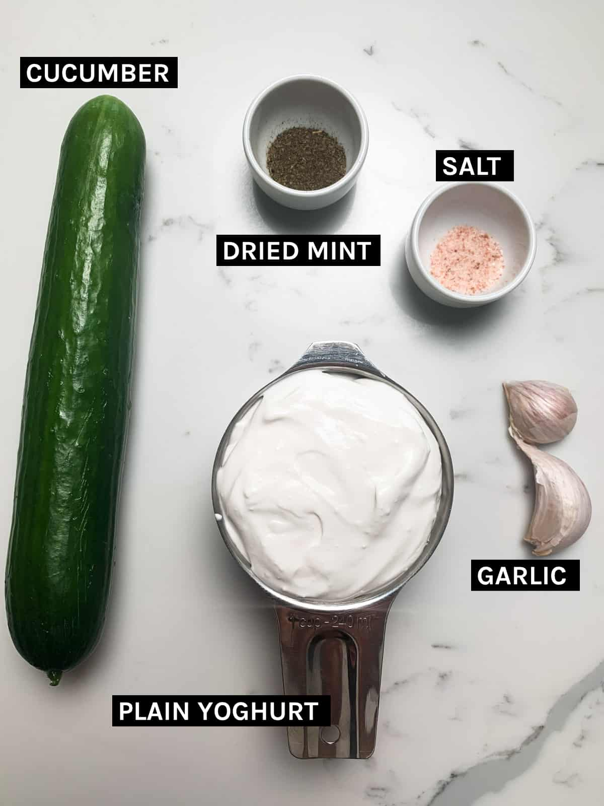 yoghurt cucumber salad ingredients laid out on a white bench